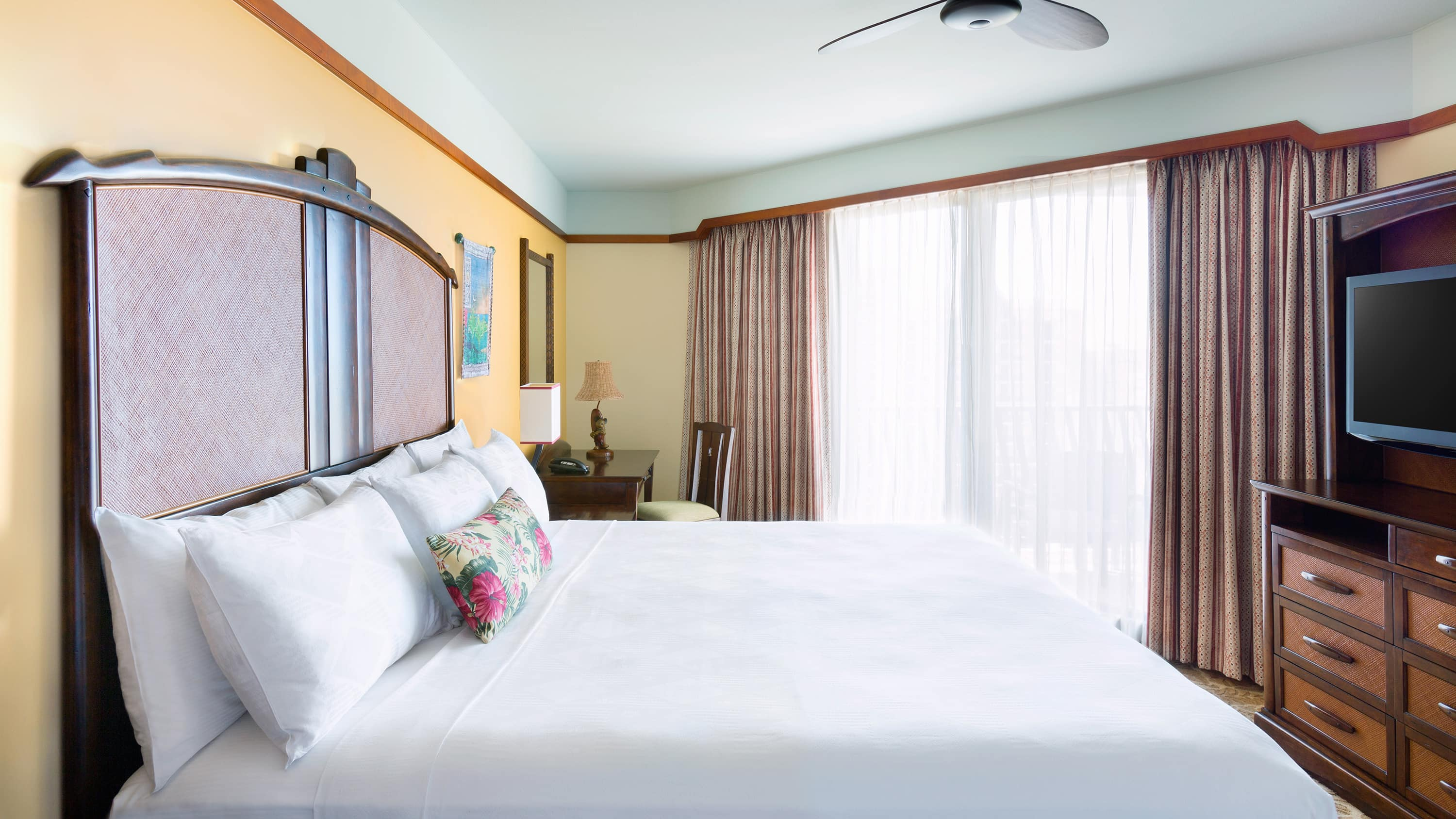 A room with a bed, a TV, a mirror, 2 lamps, a fan and curtains