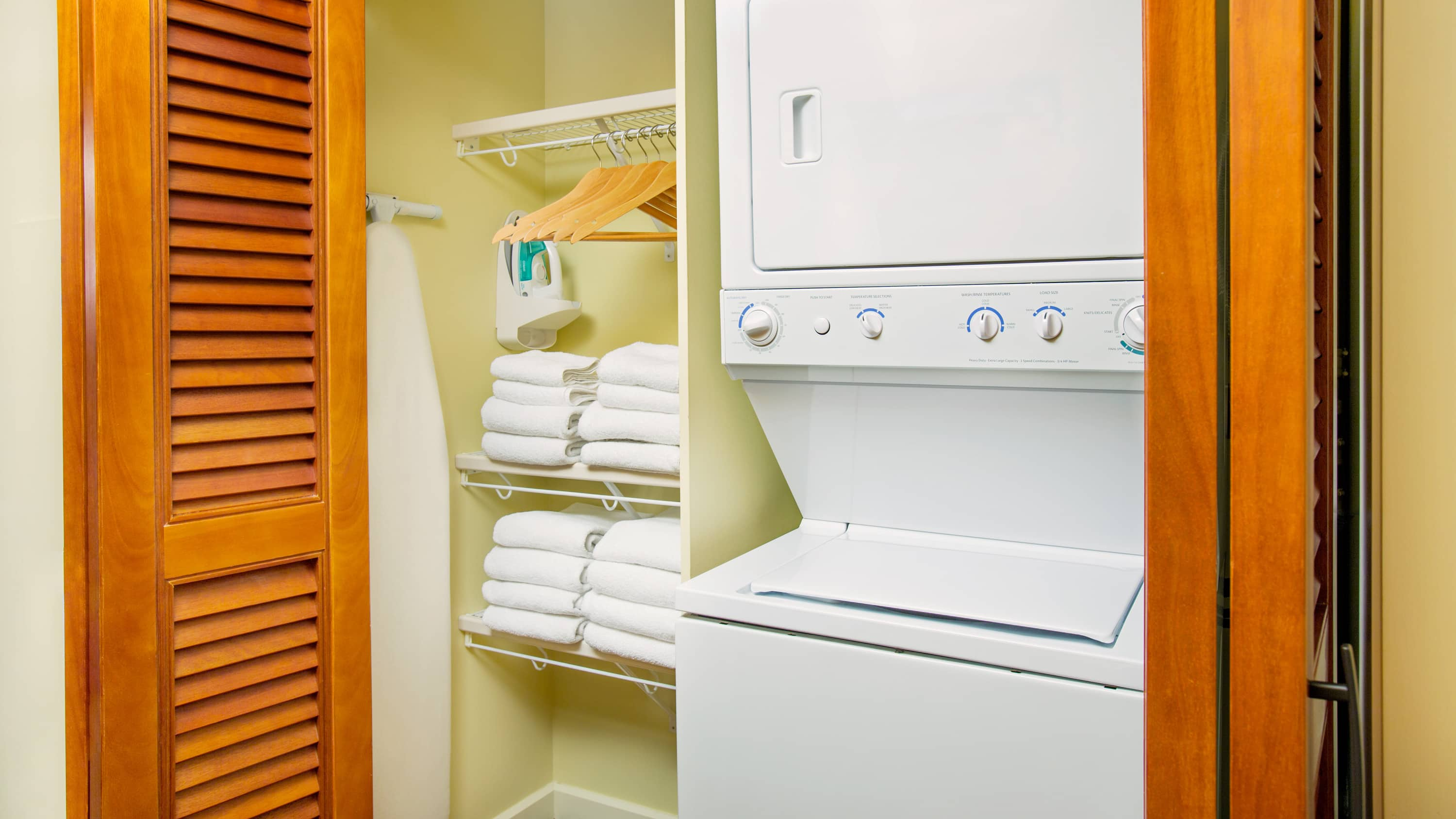 A washer and dryer near shelves with clothes hangers and towels