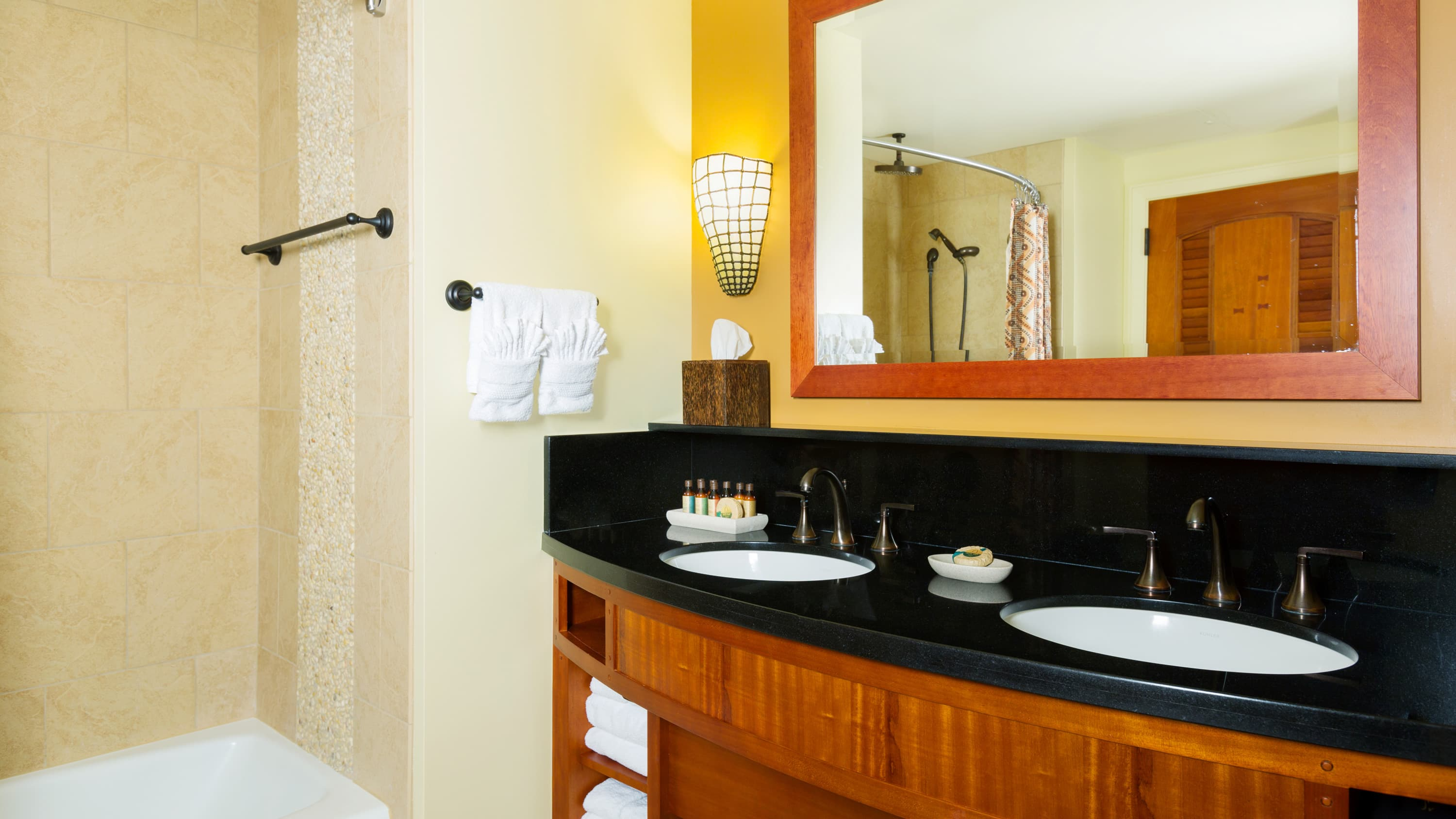 A sink with towels, a mirror and toiletries near a bathtub