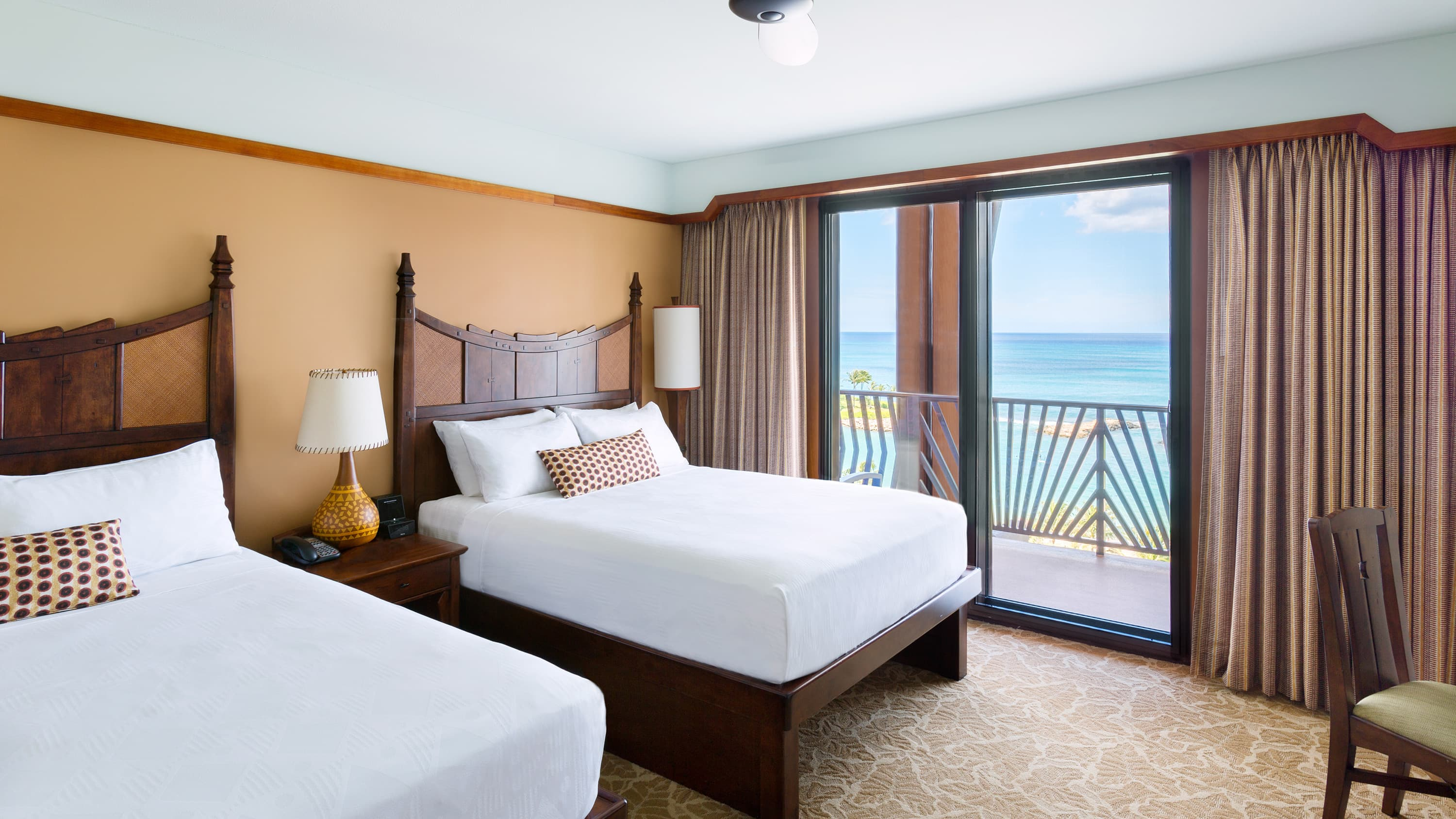 A king bed opposite a dresser with flat-panel TV and a table and chair, with an ocean view balcony beyond