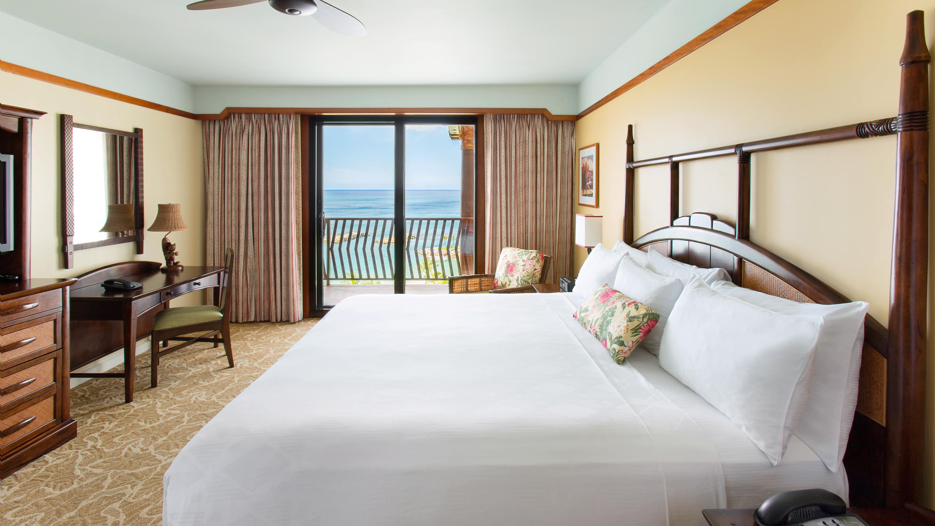 Two queen beds opposite a dresser with flat-panel TV and a table for 2, with an ocean view balcony beyond