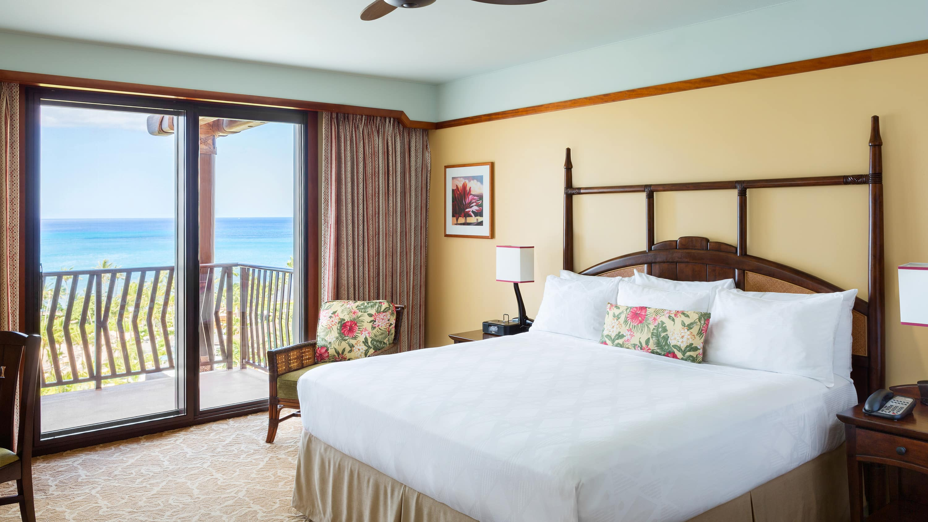 A room with a bed, a runner, 2 chairs, balcony access and towels folded to resemble a Mickey Mouse head