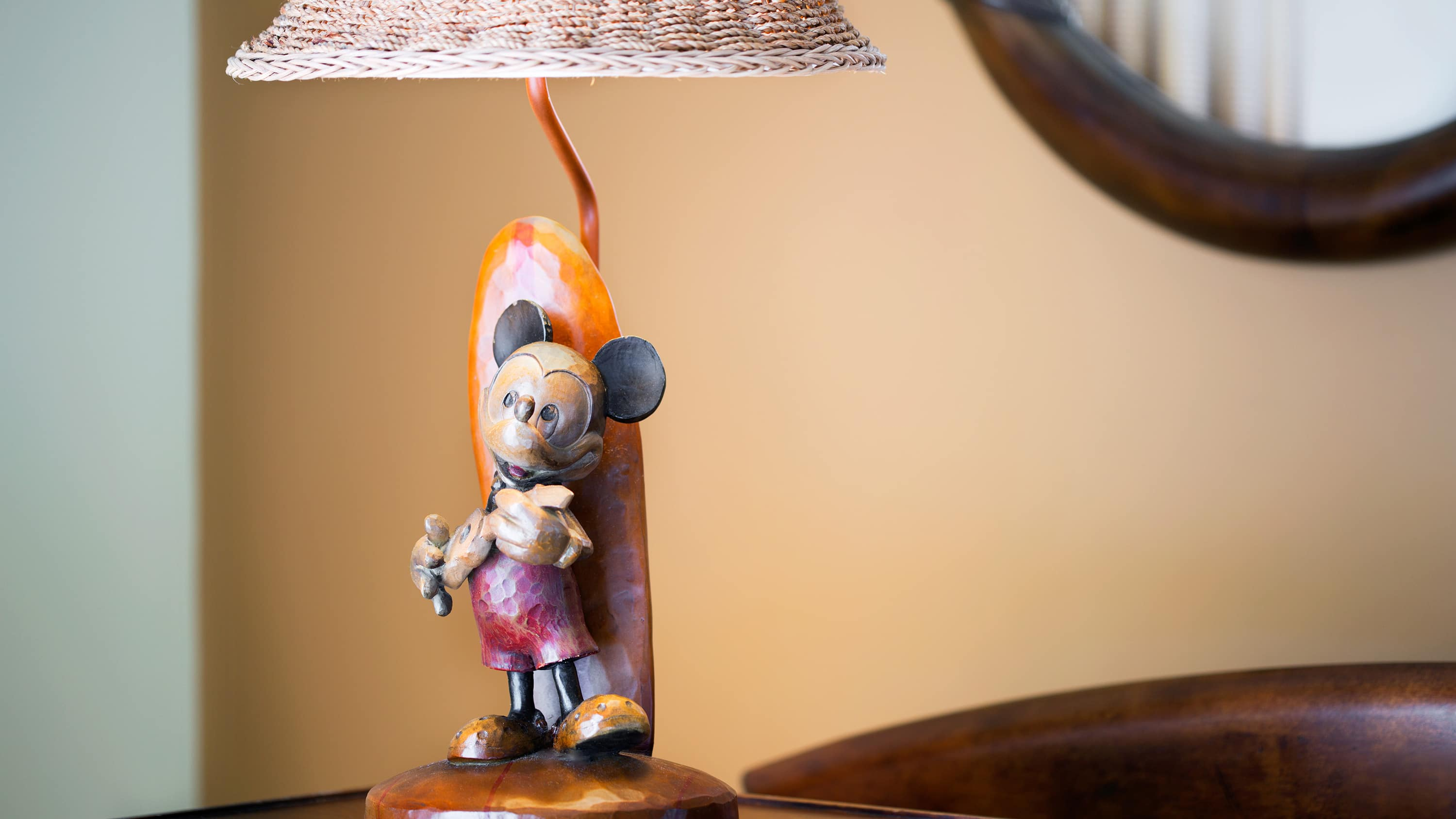 A wooden lamp carved to resemble Mickey Mouse with a ukulele near a surfboard