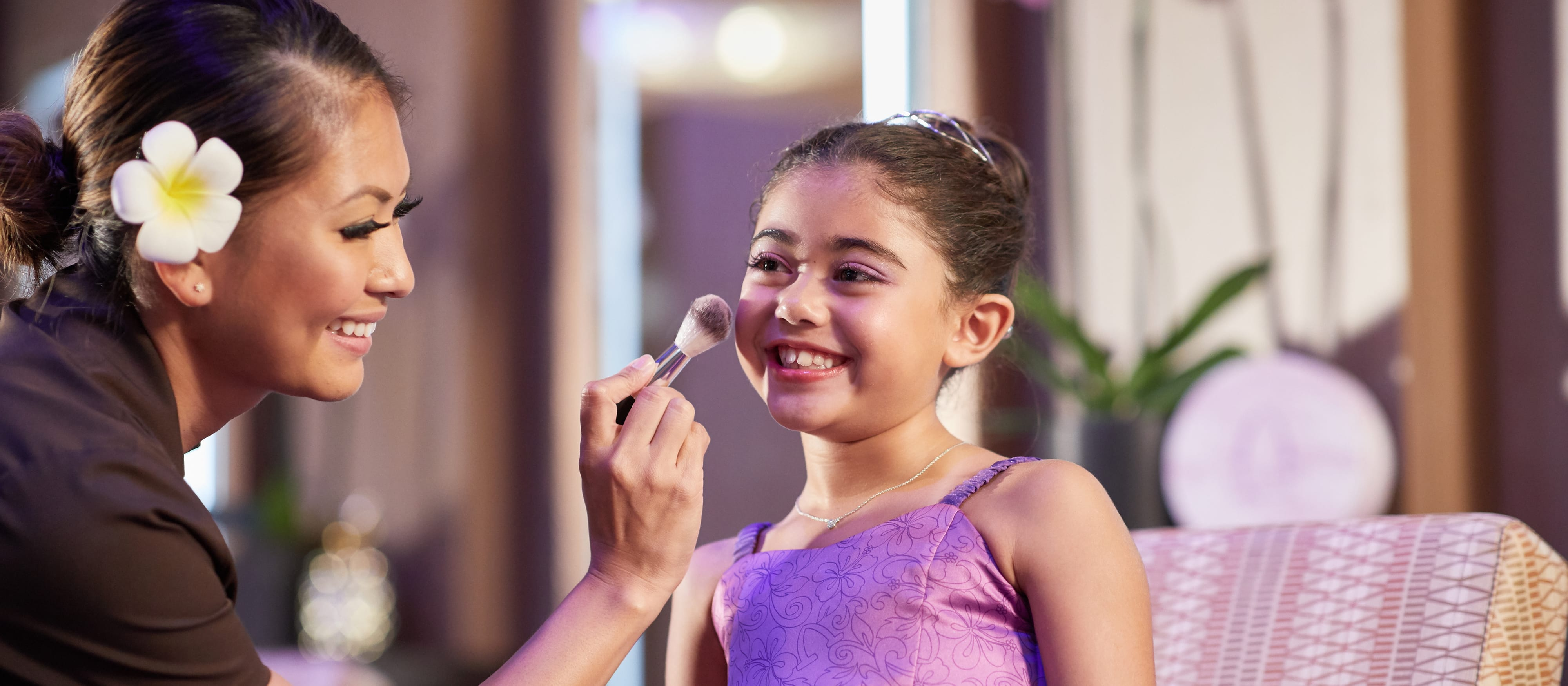 A Painted Sky: HI Style Studio stylist with a flower behind her ear applies makeup to a smiling young girl at Painted Sky: HI Style Studio at Aulani Resort
