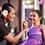 A Painted Sky, HI Style Studio stylist with a flower behind her ear applies makeup to a smiling young girl at Painted Sky: HI Style Studio at Aulani Resort