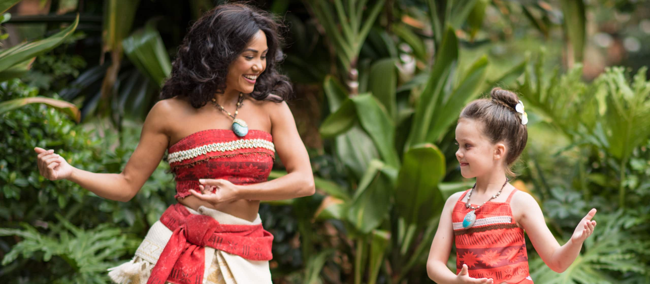 A Hawaiian hula dancer teaches the hula to a girl who is dressed in traditional Hawaiian clothes