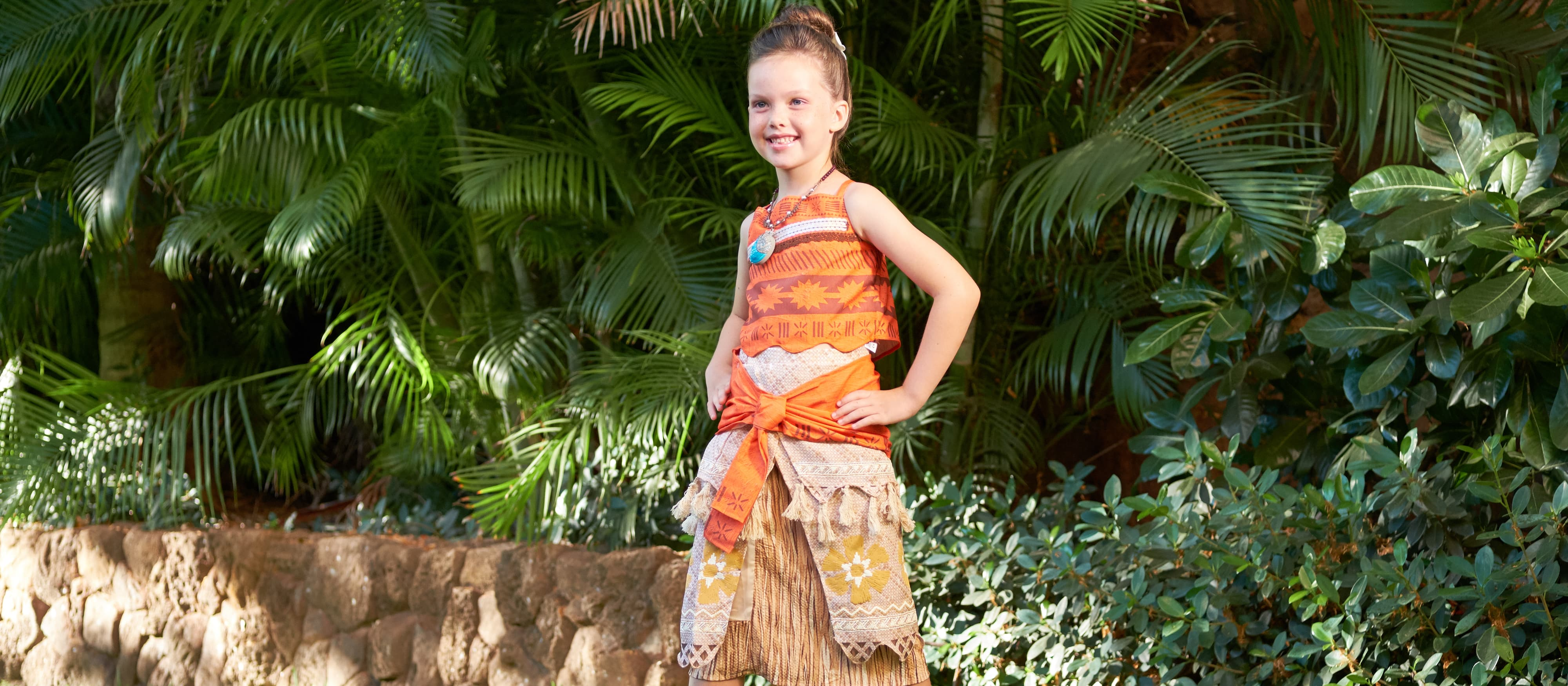 A young girl in a Moana costume poses in front of some foliage