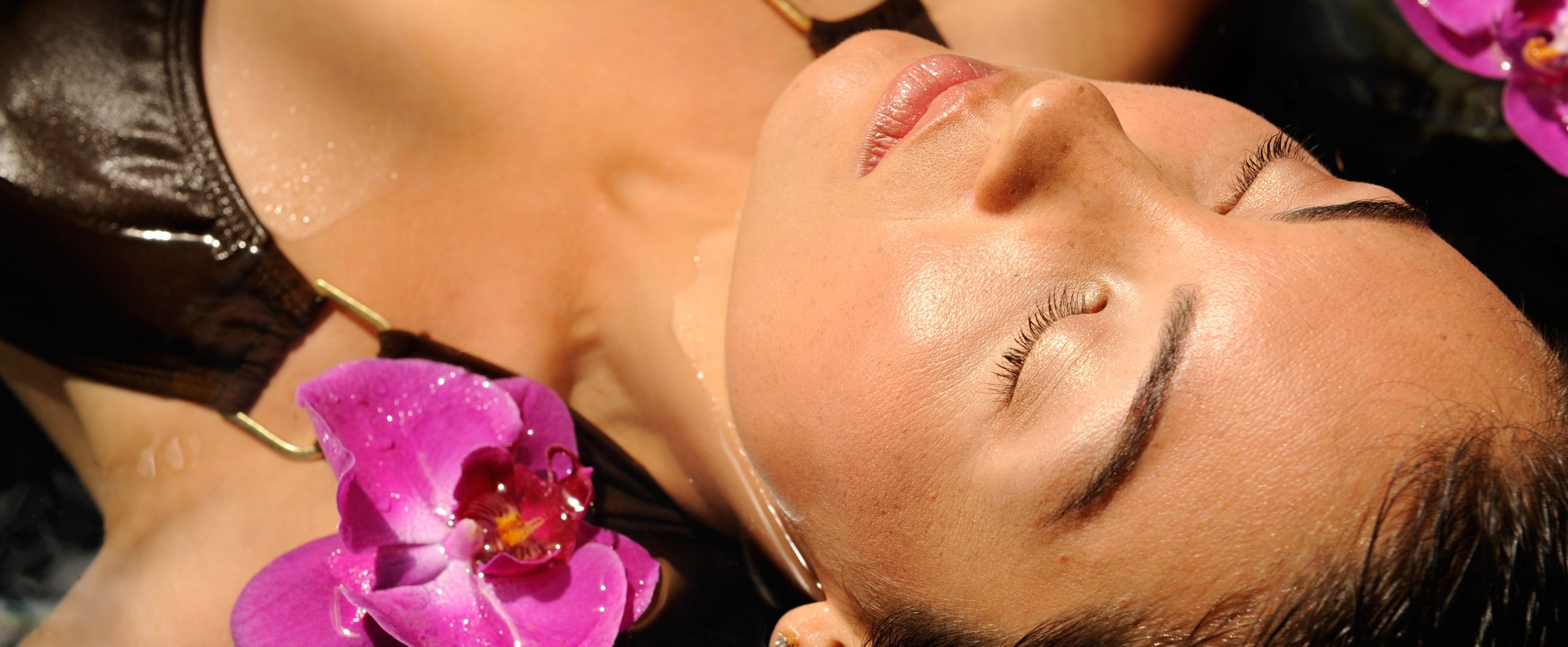 水の中で目を閉じて横たわる女性とその顔のまわりに浮かぶ蘭の花