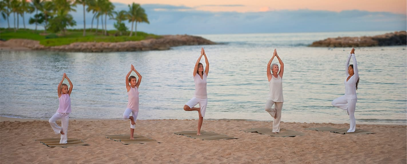 Several Guests practice yoga poses on the Aulani beach
