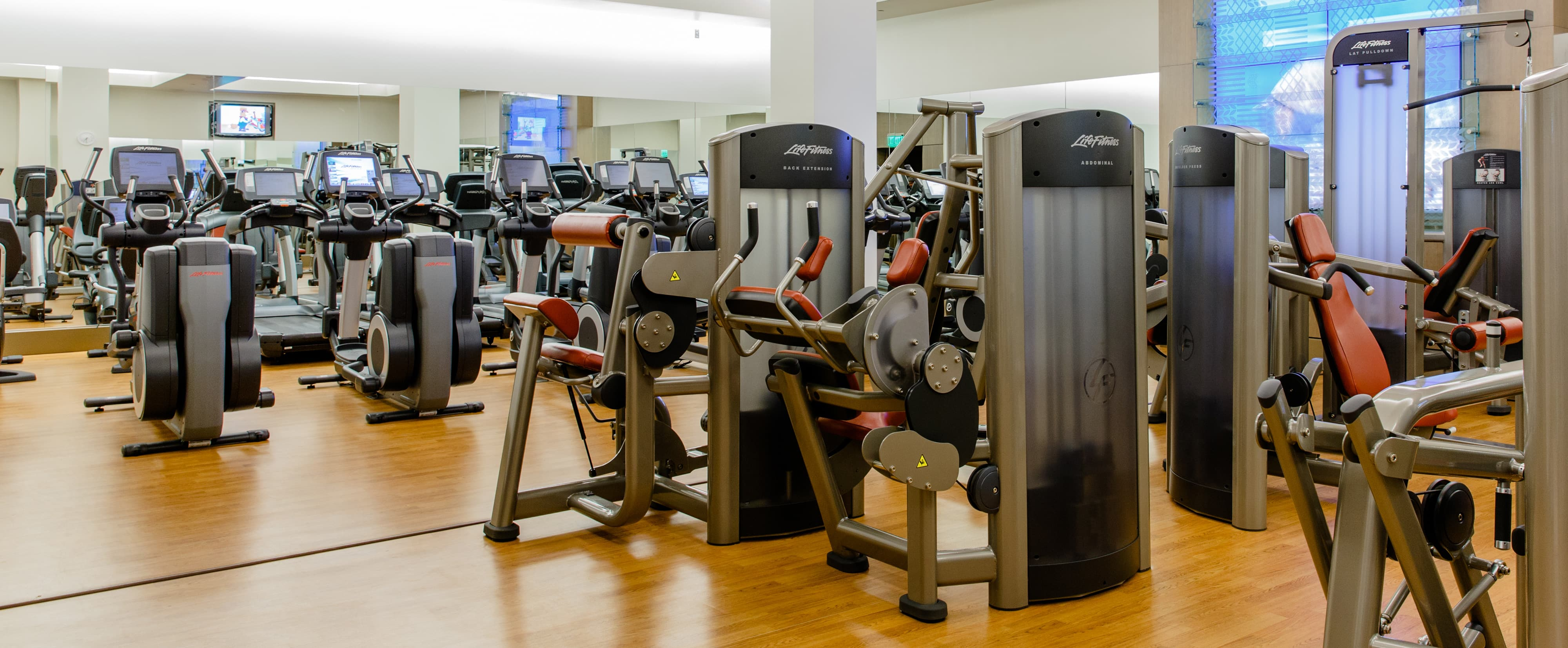 Life Fitness elliptical machines along a mirrored wall inside Mikimiki Fitness Center