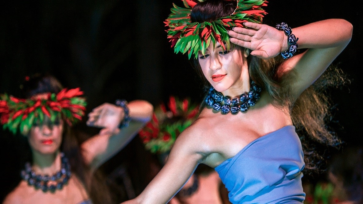 A group of Hawaiian women in traditional outfits and leafy head dresses perform an island dance at the Ka Wa'a Luau