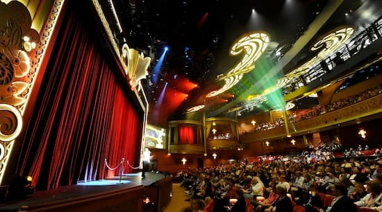 """On Friday, Cruise Director Rachel Quinn introduces """"The Golden Mickeys: A Timeless Tribute,"""" one of three stage shows presented in the Walt Disney Theatre"""