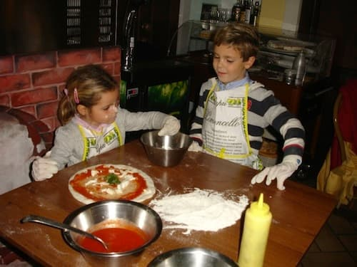 Kids enjoy authentic Italian cuisine by making their own pizza in Naples