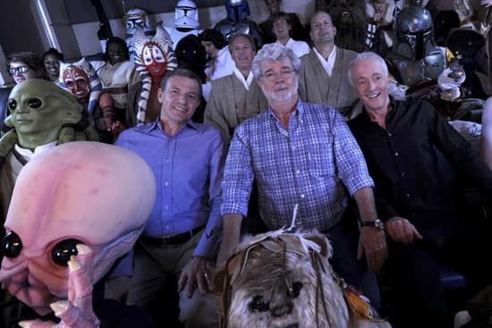 Walt Disney Co. president and CEO Bob Iger (left) 'Star Wars' creator George Lucas (center) and actor Anthony Daniels, who portrayed C-3PO in 'Star Wars' (right), pose with 'Star Wars' characters May 20, 2011 inside a 'Star Tours' ride vehicle at Disney's Hollywood Studios theme park in Lake Buena Vista, Fla. during grand opening ceremonies for 'Star Tours -- The Adventures Continue,' a new 3-D attraction based on the 'Star Wars' films. The attraction, which features more than 50 possible random ride experiences, opened May 20, 2011 at Walt Disney World in Florida and will open June 3, 2011 at Disneyland Resort in California. (David Roark, photographer)
