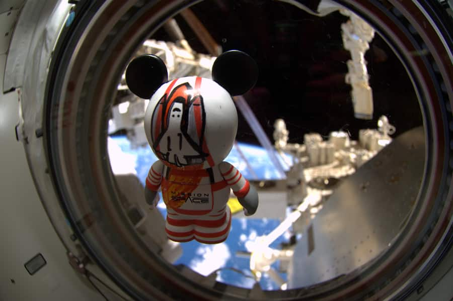 The customized Mission:SPACE-inspired Vinylmation, looks to the Earth as it floats inside Space Shuttle Atlantis
