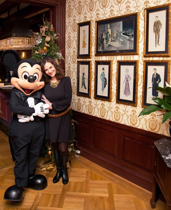 Lesley Ann Warren and Mickey Mouse Stand Near the Costume Sketches Hanging on the Wall at Club 33 at Disneyland Park