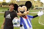Soccer Player Lionel Messi Kicks Off a Game with Mickey Mouse