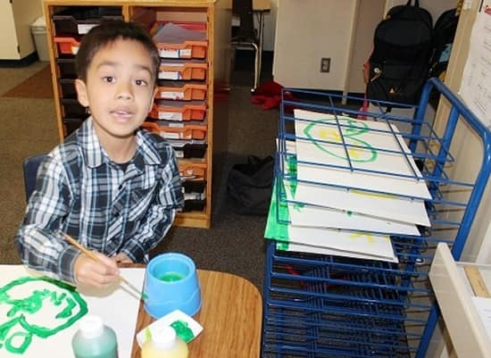A Student Learning With New Art Supplies Like Paints and a Drying Rack
