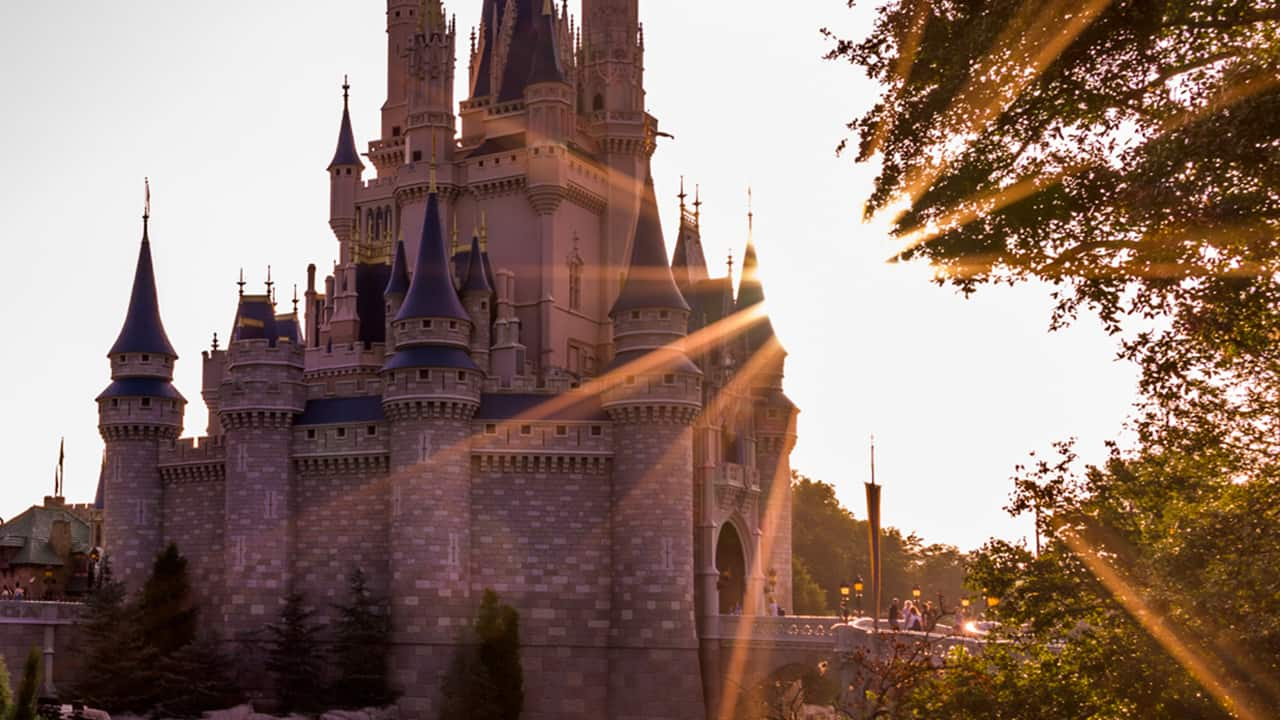 Disney World castle with sun rising over it
