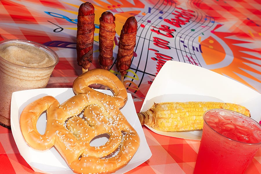 "Mickey-shaped pretzels, ""Wrap""sody in Bacon BBQ bacon-wrapped hot dogs and ""Corn""certo on the Cob chili lime elote at JamminBacklot at Disney California Adventure Park"
