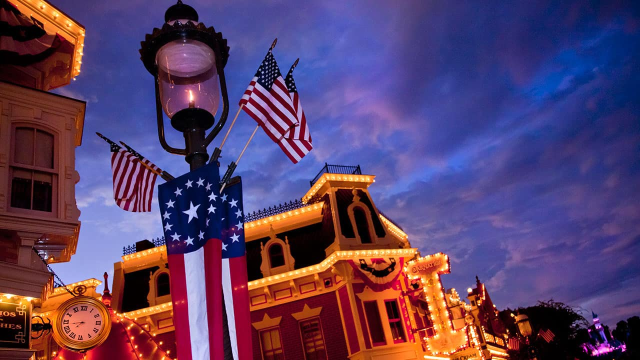 Lamppost at Disneyland at dusk with American flags hanging from it