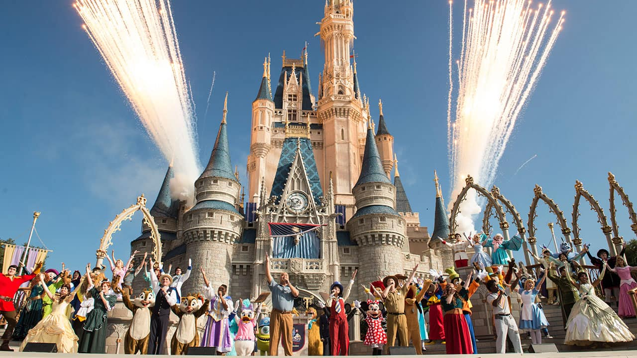 """Walt Disney World President George A. Kalogridis, surrounded by a flurry of beloved Disney characters, addresses Magic Kingdom Park guests during the 45th anniversary of Walt Disney World, Saturday, Oct. 1, 2016. The celebration hit a high note with a special live arrangement of """"When You Wish Upon a Star,"""" underscored by a burst of pyro magic and colorful streamers shot high above the Kingdom. (David Roark, photographer)"""