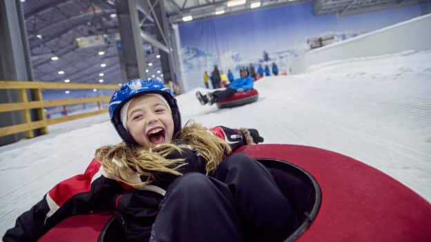 Kids enjoy snow tubing in Cologne, Germany at indoor winter park on Adventures by Disney Rhine River Cruise