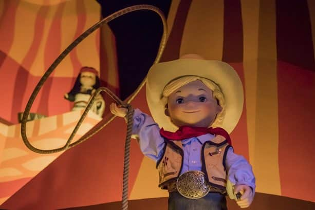 A cowboy lassoing with red rock formations behind him at it's a small world at Disneyland park