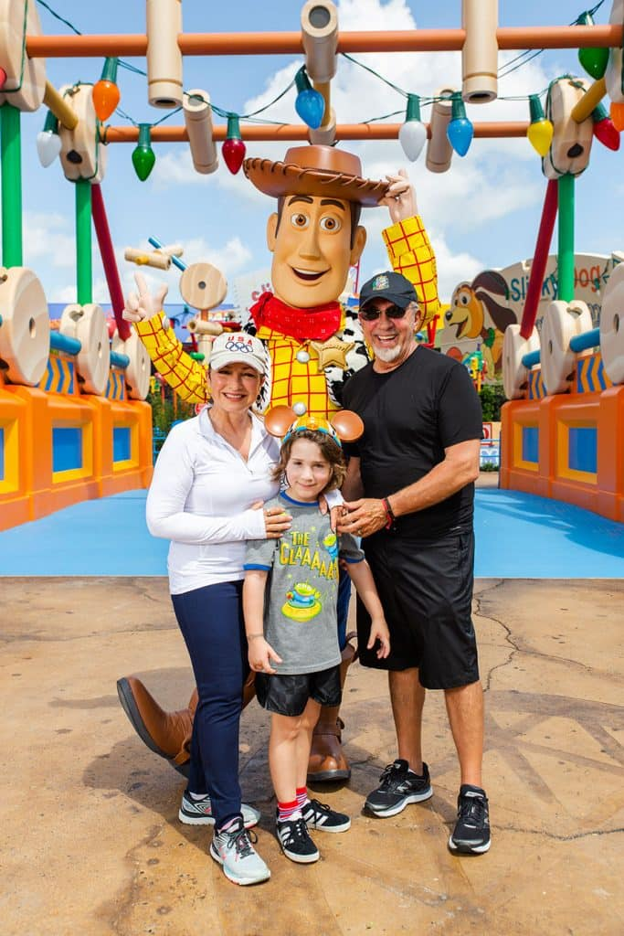 Gloria and Emilio Estefanand their grandson Sasha pose with Woody in Toy Story Land at Disney's Hollywood Studios