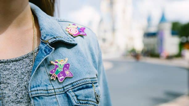 Play Disney Parks wearable achievement pins on a jean jacket