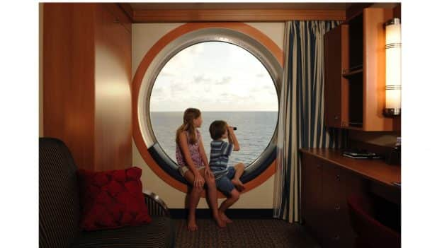 Kids looking out a window on Disney Cruise Line