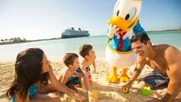 Family building sandcastles on beach on Disney Cruise Line's Castaway Cay with Donald Duck