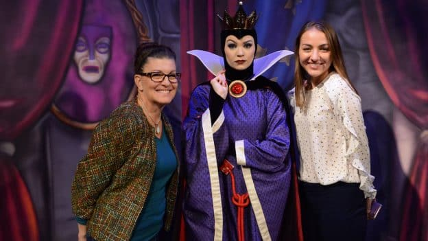 Two women pose with the Evil Queen for a photo