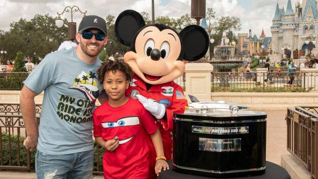 Defending Daytona 500 Champion Austin Dillon with young fan Jordan Wade and Mickey Mouse at Magic Kingdom Park