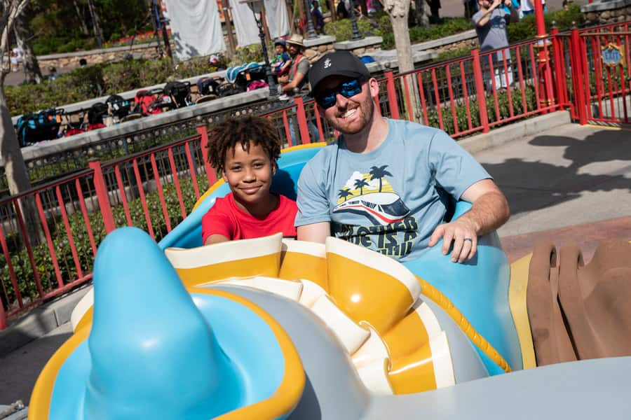 Defending Daytona 500 Champion Austin Dillon and young fan Jordan Wade ride Dumbo the Flying Elephant at Magic Kingdom Park