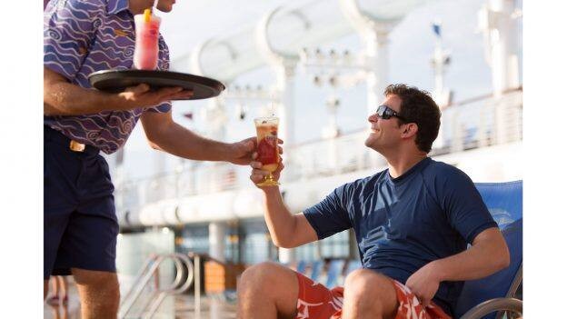 Crew member serving a drink to a guest onboard Disney Cruise Line