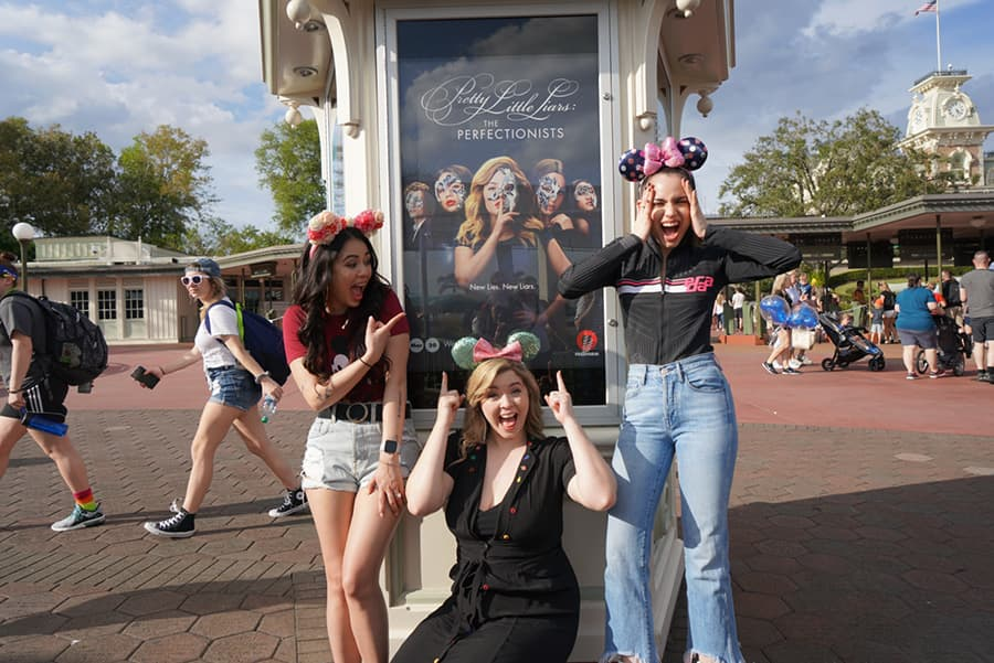 Sasha, Janel, and Sofia in front of the 'Pretty Little Liars: The Perfectionists' poster outside the Magic Kingdom entrance.