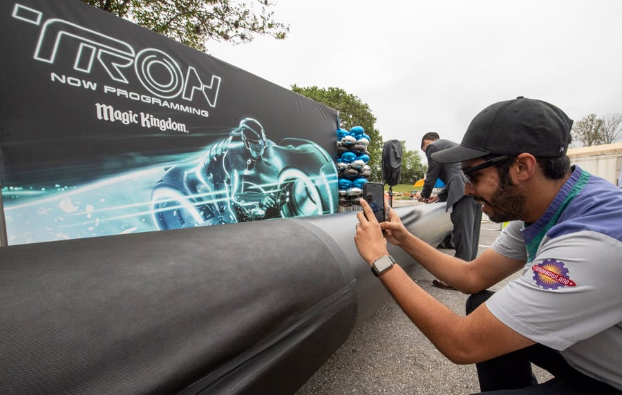 TRON attraction construction milestone at Magic Kingdom park - cast member signs name on first steel support columns for the new attraction