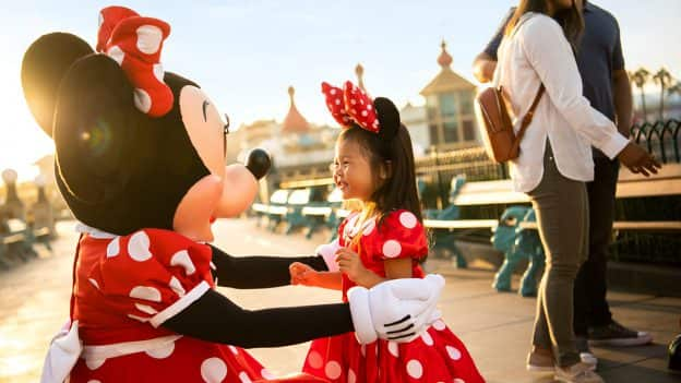 Minnie Mouse hugs young girl dressed as Minnie Mouse at Disney California Adventure park