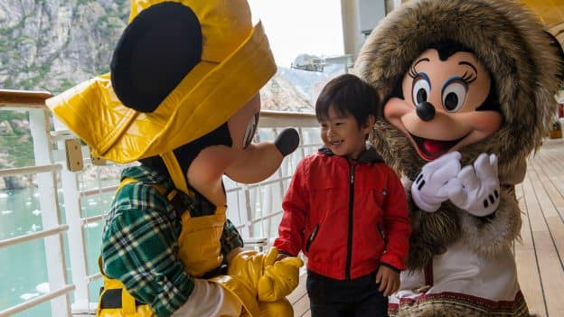 Mickey Mouse and Minnie Mouse meet a young guest aboard Disney Cruise Line in Alaska