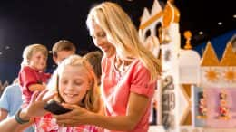Mom and daughter look at smartphone in the queue for it's a small world at Magic Kingdom Park