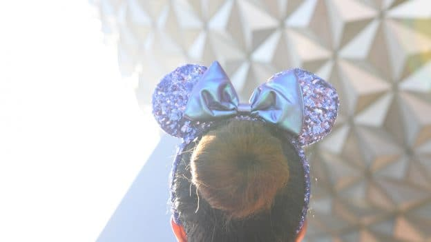 Purple Minnie Mouse ear headbands in front of Spaceship Earth