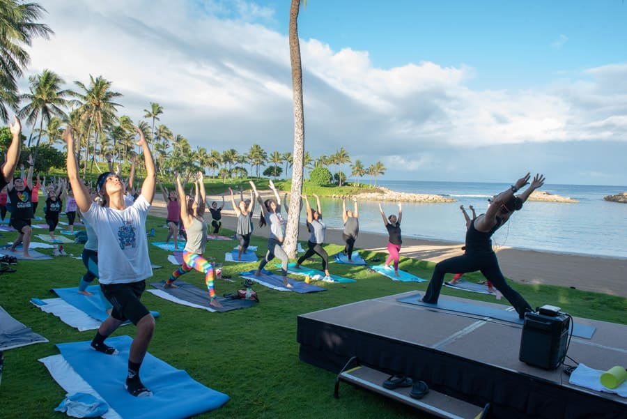 Cast members at Aulani, A Disney Resort & Spa have a yoga session on the beach in the morning to celebrate International Yoga Day