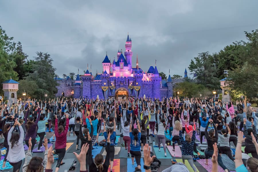Cast members have a calming yoga session at Sleeping Beauty Castle at Disneyland Resort
