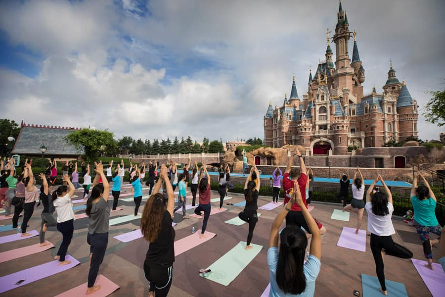 Cast members at Shanghai Disney Resort stretched out at Enchanted Storybook Castle for a mindful yoga session.