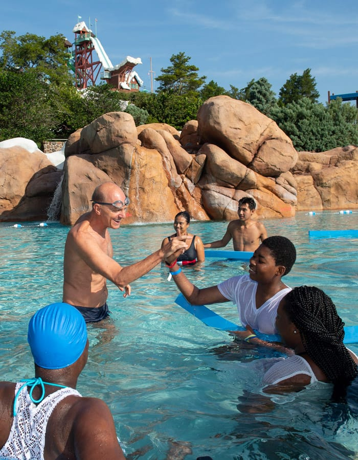 """Olympic gold medal swimmer Rowdy Gaines talks with swimmers at the 2019 """"World's Largest Swimming Lesson"""" event at Disney's Blizzard Beach"""
