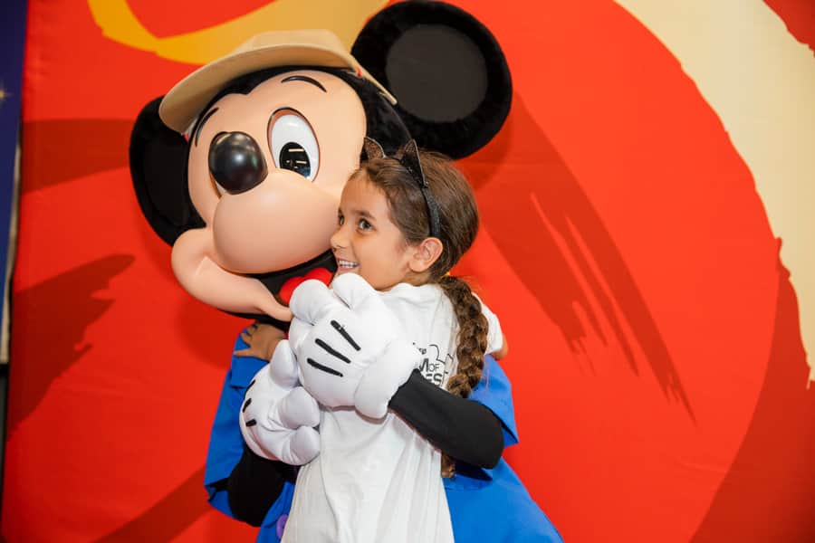 Mickey Mouse and a child hug during A Gift For Teaching Back-to-School Kids and Family Day