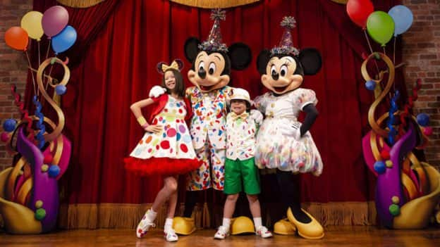 Mickey Mouse and Minnie Mouse greet guests together in Town Square Theater as part of Mickey & Minnie's Surprise Celebration at Magic Kingdom Park
