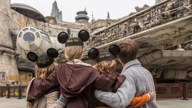 Guests wearing Mickey Ears pose in Star Wars: Galaxy's Edge at Disneyland park