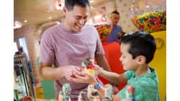 Father and son look at treats in Vanellope's Sweets and Treats aboard the Disney Dream